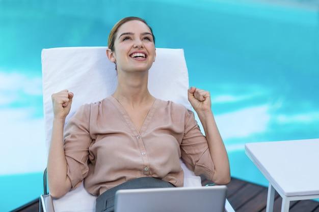 Opgewekte vrouw met laptop dichtbij pool