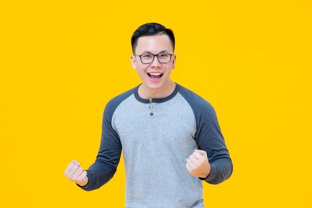 Opgewekte winnaar aziatische mens die zijn vuisten met het glimlachen gezicht opheffen