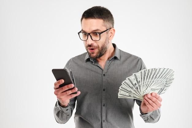 Opgewekte zakenman die het mobiele geld van de telefoonholding gebruiken.