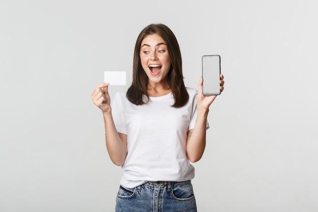 Opgewonden aantrekkelijk meisje dat het smartphonescherm en witte creditcard toont.