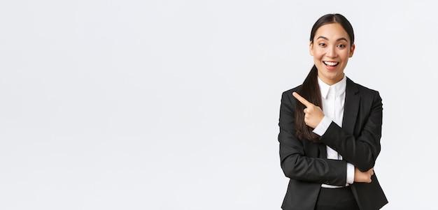 Opgewonden aantrekkelijke aziatische vrouwelijke verkoopster, makelaar in pak die perfect huis suggereert, in pak staat en met de vinger naar links wijst. zakenvrouw die aankondiging doet, banner toont