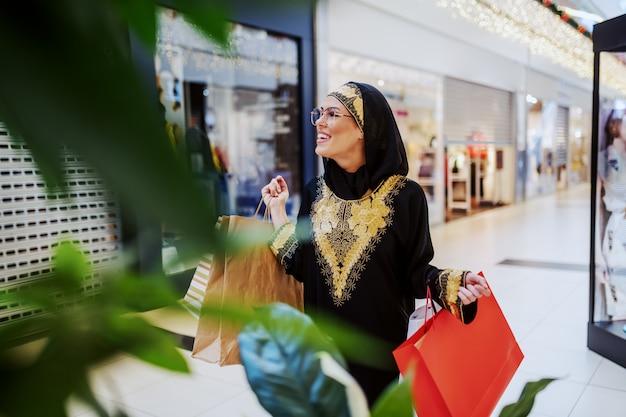 Opgewonden aantrekkelijke moslimvrouw wandelen in winkelcentrum met boodschappentassen in handen en op zoek naar een andere mooie jurk voor haar.