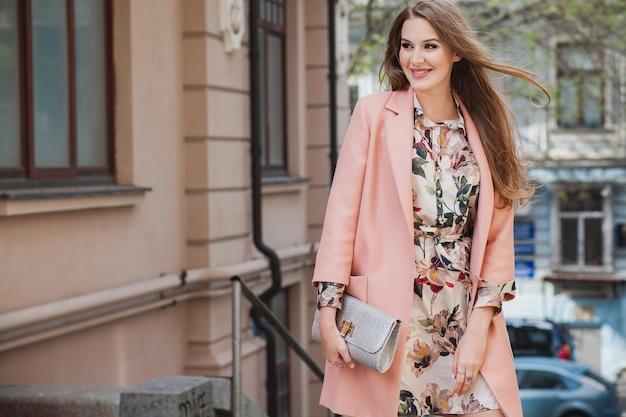 Opgewonden aantrekkelijke stijlvolle lachende vrouw lopen stad straat in roze jas lente modetrend bedrijf portemonnee