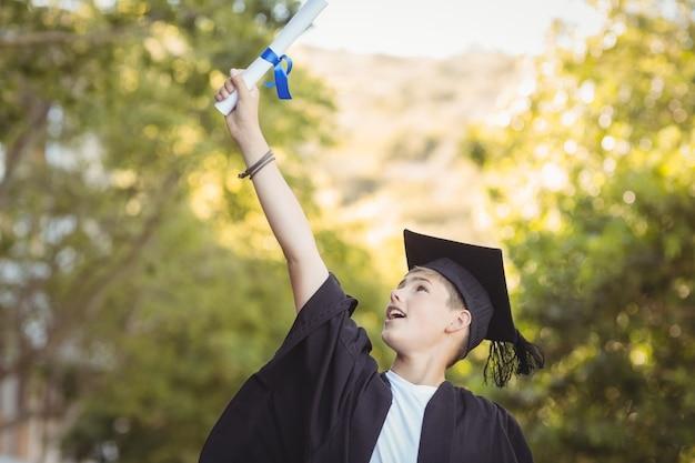 Opgewonden afgestudeerde schooljongen met gradenrol op de campus