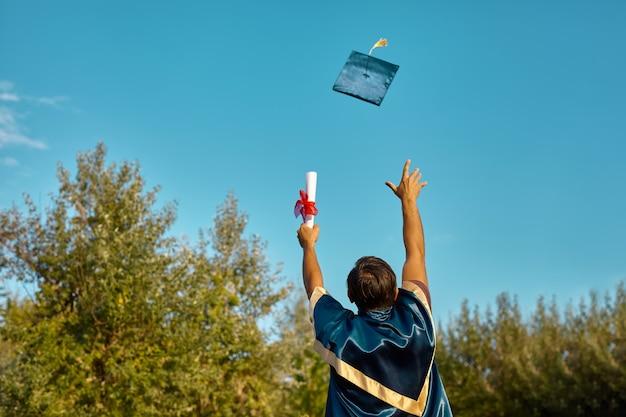 Opgewonden afgestudeerde student in jurk met opgeheven handen met diploma over blauwe lucht en gooit de hoed in de lucht