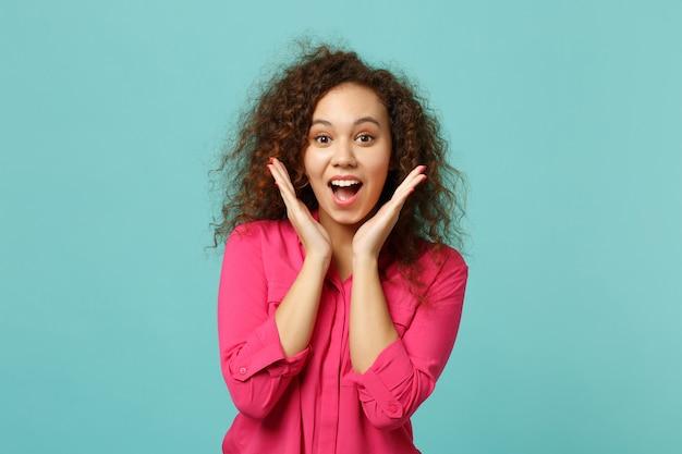 Opgewonden afrikaans meisje in roze vrijetijdskleding die mond open houdt, handen uitspreidt die op blauwe turkooizen muurachtergrond in studio worden geïsoleerd. mensen oprechte emoties, lifestyle concept. bespotten kopie ruimte.