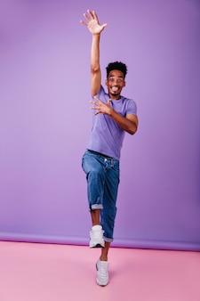 Opgewonden afrikaans model in witte schoenen dansen. indoor shot van zorgeloze brunette man draagt paars t-shirt.