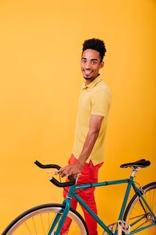 Opgewonden afrikaanse man in stijlvolle kleding poseren met groene fiets. binnenfoto van glimlachende zwarte kerel die met fiets geniet.