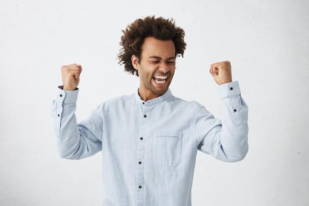 Opgewonden afrikaanse mannelijke winnaar die zijn vuisten met groot geluk opheft met een goed humeur
