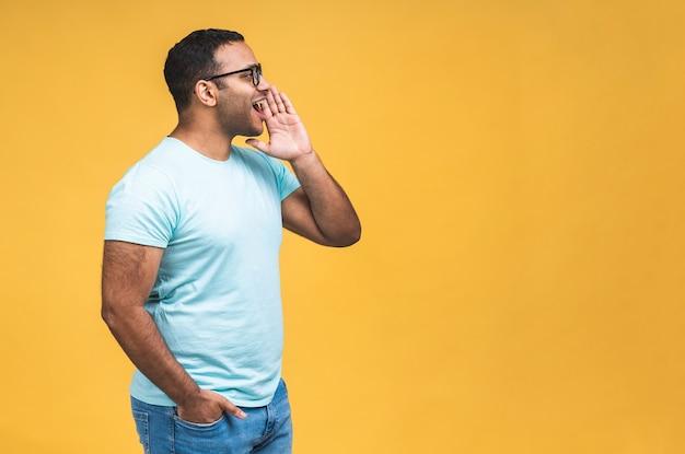 Opgewonden afro-amerikaanse indiase zwarte man in glazen geïsoleerd over gele achtergrond schreeuwen op lege kopie ruimte opzij, glimlachende zwarte man maakt luidspreker schreeuw vertellen over goede verkoopaanbieding of deal