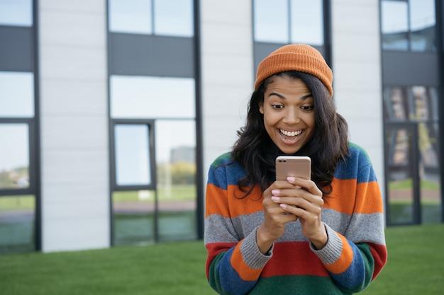 Opgewonden afro-amerikaanse man met behulp van mobiel