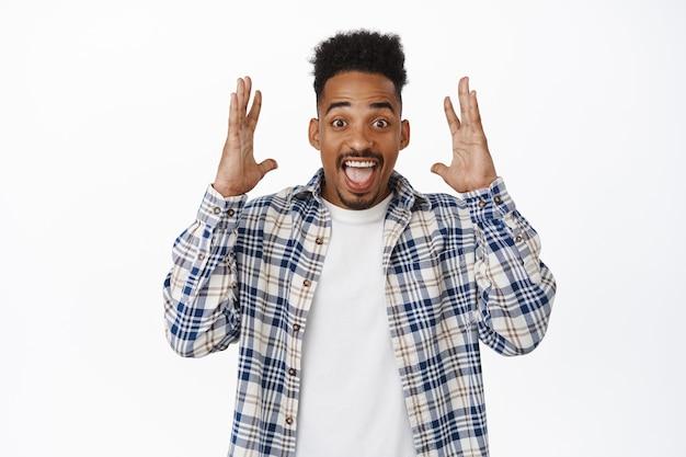 Opgewonden afro-amerikaanse man vertelt groot nieuws. opgewonden zwarte man die handen schudt in de buurt van hoofd en schreeuwaankondiging, geweldige verkooppromotie, staande op wit