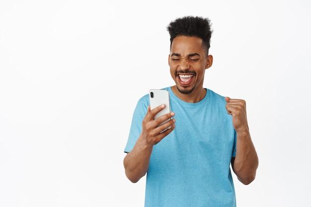 Opgewonden afro-amerikaanse man vuist pomp, online geld winnen, vreugde met smartphone in de hand, ja zeggen met vreugde en kijken naar mobiele telefoon app scherm op wit
