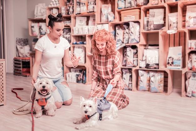 Opgewonden alvorens te kopen. roodharige vrouw met krullen voelt zich opgewonden voordat ze speciale kleding voor huisdieren koopt