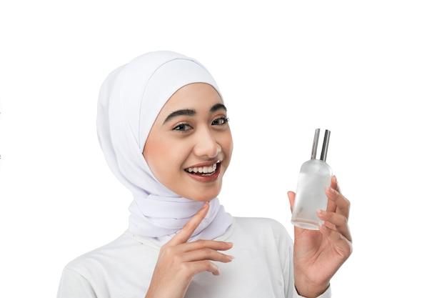 Opgewonden aziatisch hijab-meisje in witte jurk met een fles serum met handgebaar