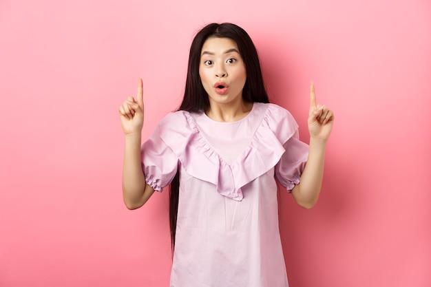 Opgewonden aziatisch meisje toont geweldig promo-aanbod, wijzende vingers omhoog en hijgend verbaasd, staande op roze achtergrond.