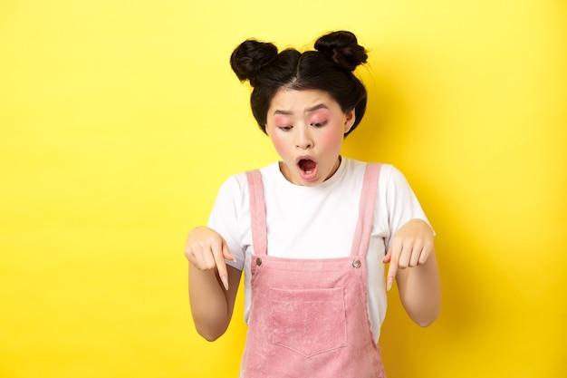Opgewonden aziatisch tienermeisje dat reclame bekijkt, vingers naar beneden wijst en verbaasd kaak laat vallen, promo-aanbieding toont, geel.