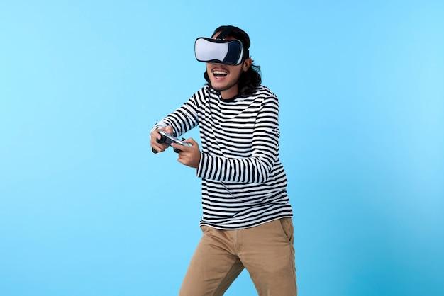 Opgewonden aziatische man met 3d-bril spelen van videogame op blauwe ruimte.