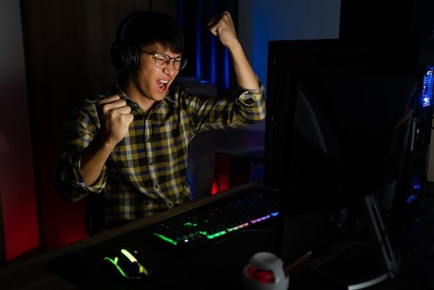 Opgewonden aziatische man pro gamer aan de tafel zitten, spelen en winnen in online videogames op een computer en smartphone, technologie gaming cyber of e-sport kampioenschap concept.