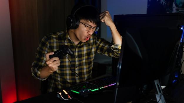 Opgewonden aziatische man pro gamer zittend aan tafel, spelen en winnen in online videogames op een computer en smartphone, technologie gaming cyber of e-sport kampioenschap concept