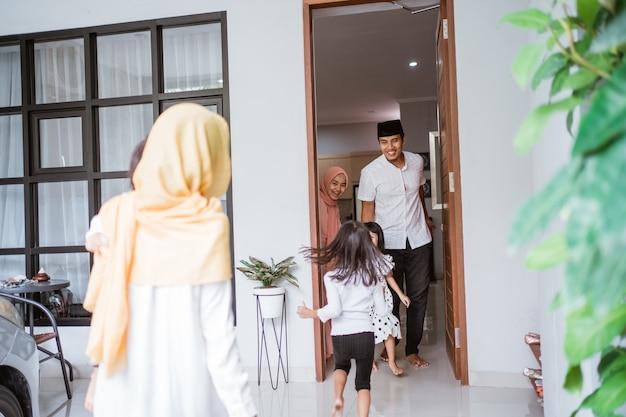 Opgewonden aziatische moslimfamilie die vriend bezoekt tijdens eid fitri mubarak thuis