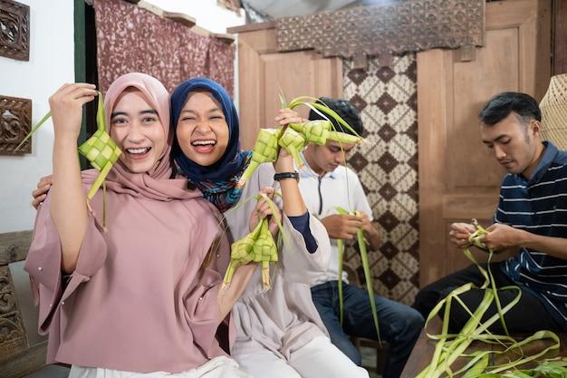 Opgewonden aziatische moslimvrouw die ketupat-rijst maakt met kokosblad tijdens ramadan kareem die zich voorbereidt op de viering van eid fitri mubarak