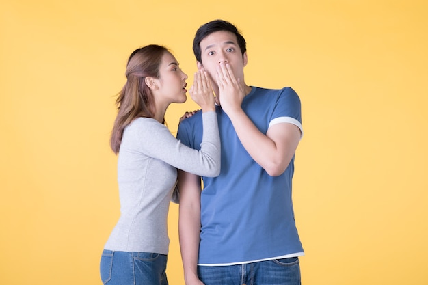 Opgewonden aziatische paar fluisteren geheimen aan elkaar geïsoleerd op gele achtergrond yellow