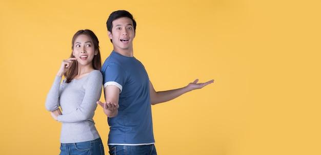 Opgewonden aziatische paar in casual kleding presenteren met handen open om ruimte geïsoleerd op gele achtergrond te kopiëren copy