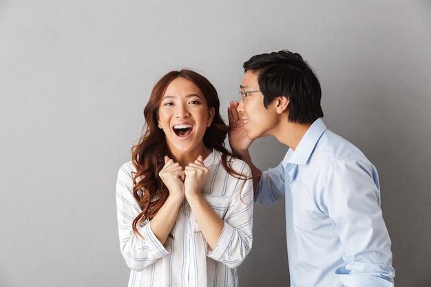 Opgewonden aziatische paar staande geïsoleerd, geheimen aan elkaar vertellen
