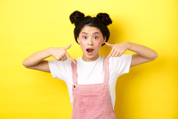 Opgewonden aziatische tienermeisje met schoonheidsmake-up, wijzende vingers naar beneden en open mond gefascineerd, permanent gelukkig op geel.