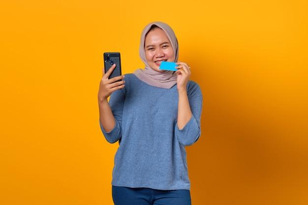 Opgewonden aziatische vrouw die smartphone vasthoudt en creditcard bijt op gele achtergrond