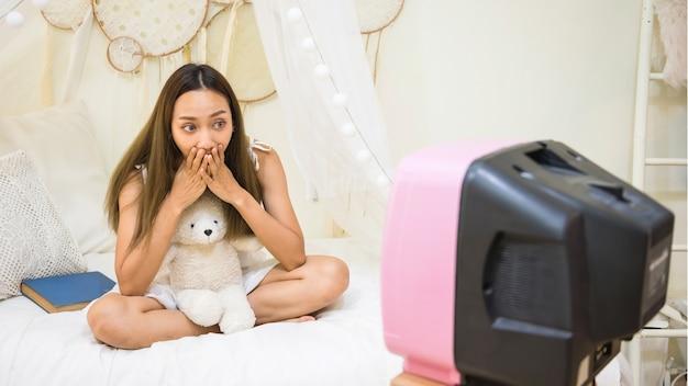 Opgewonden aziatische vrouw horrorfilm op bed