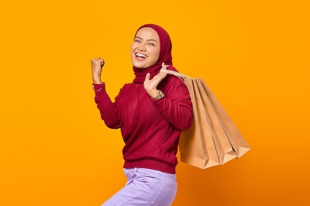 Opgewonden aziatische vrouw met boodschappentassen met triomfantelijke uitdrukking op gele achtergrond