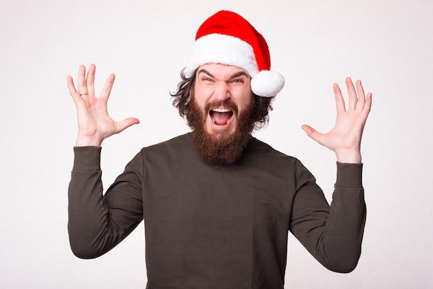 Opgewonden bebaarde hipster man in trui met kerstman hoed schreeuwen en gebaren