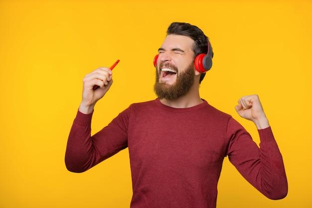 Opgewonden bebaarde man, genietend van zijn favoriete liedje met nieuwe koptelefoon, dansend op gele achtergrond