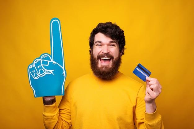 Opgewonden bebaarde man houdt een creditcard of bankpas en draagt een handschoen van schuimventilator.