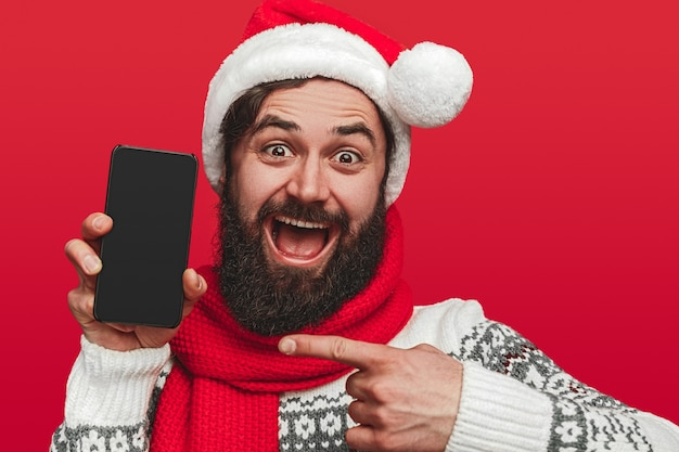 Opgewonden bebaarde man in kerstmuts wijzend op smartphone