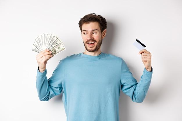 Opgewonden bebaarde man kiezen tussen geld en plastic creditcard, betaling met contant geld of contactloos, permanent op witte achtergrond.