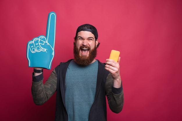 Opgewonden bebaarde mannelijke hipster draagt een handschuimhandschoen en zijn telefoon gilt