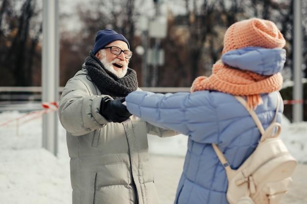 Opgewonden bebaarde oude man in winterjas glimlacht naar de bejaarde vrouw terwijl hij haar handen vasthoudt en ronddraait in dans
