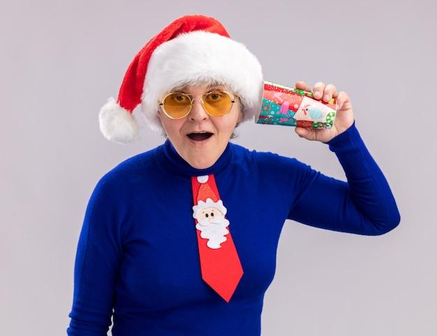 Opgewonden bejaarde vrouw in zonnebril met kerstmuts en kerst stropdas papier beker dicht bij oor te houden