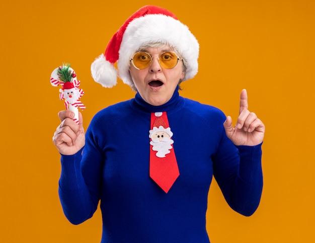 Opgewonden bejaarde vrouw in zonnebril met kerstmuts en stropdas santa houdt riet van het suikergoed en wijst omhoog geïsoleerd op een oranje achtergrond met kopie ruimte