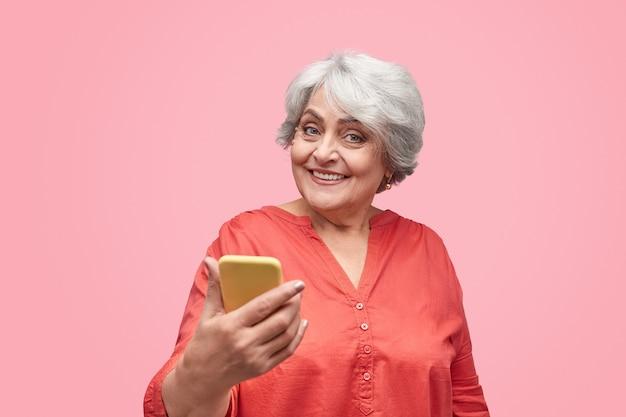Opgewonden bejaarde vrouw met smartphone