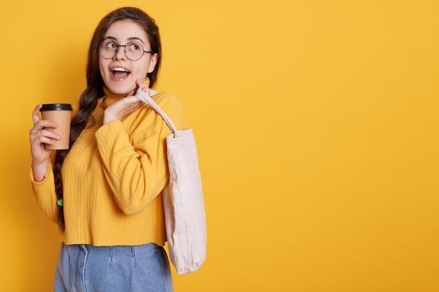 Opgewonden blanke jonge vrouw met gelukkige gezichtsuitdrukking, winkelen in winkelcentrum en afhaalmaaltijden koffie drinken. kopieer ruimte voor reclame of promotietekst.