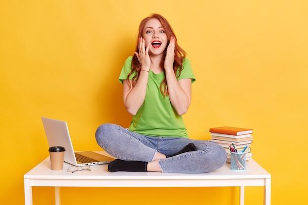 Opgewonden blanke meisje freelancer zittend op bureau geïsoleerd op gele muur. prestatiecarrière. onderwijs aan de universiteit of hogeschool