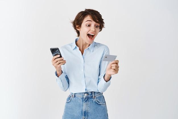 Opgewonden blanke vrouw die naar plastic creditcard kijkt en smartphone vasthoudt, staande op een witte muur
