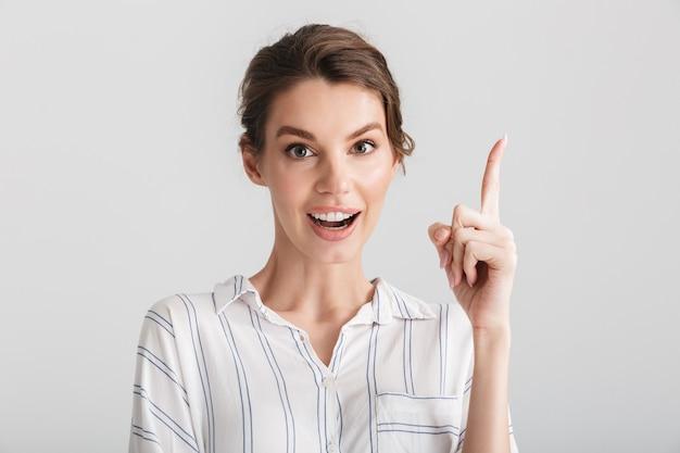 Opgewonden blanke vrouw glimlachend en wijzende vinger naar boven geïsoleerd op witte achtergrond