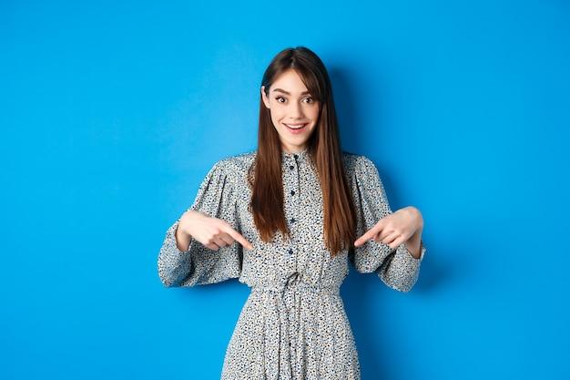 Opgewonden blanke vrouw in jurk wijzende vingers naar het logo, fantastisch nieuws en lachend, staande op blauw.