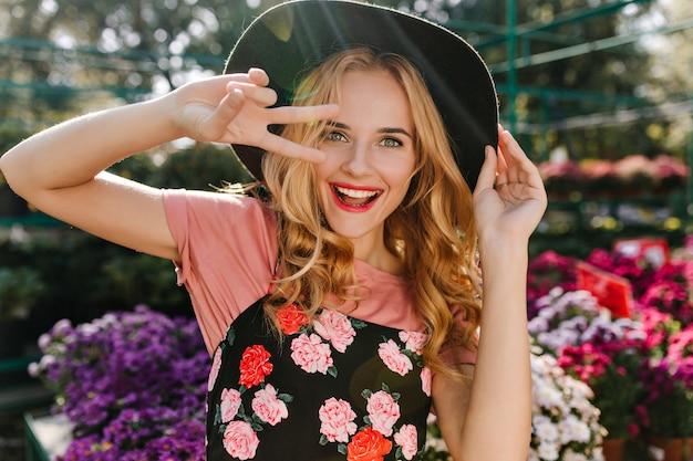 Opgewonden blanke vrouw met blinde haar plezier in kas. portret van vrolijke vrouw die in frint van bloemen danst.