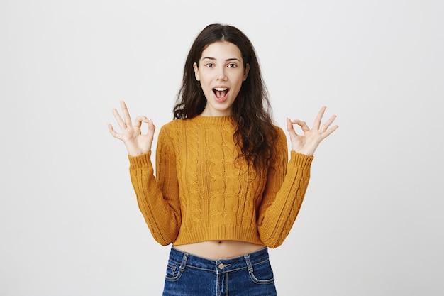 Opgewonden blij meisje toont ok gebaar, complimenteert, perfecte winkel of product aanbevelen